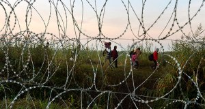 Photo Courtsey of www.dailysabah.com Migrants seen through razor wire fencing as they walk at the border between Serbia and Hungary, near Roszke, 180 kms southeast from Budapest, Hungary, 30 August 2015. EPA/Zoltan Mathe HUNGARY OUT